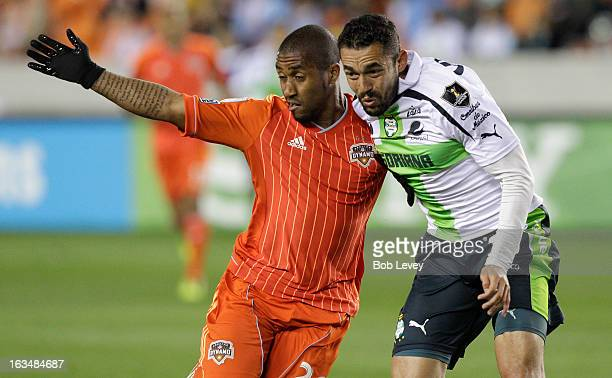 Corey Ashe of Houston Dynamo and Herculez Gomez of Santos Laguna during leg one of a CONCACAF Champions League quarterfinal match between the Houston...