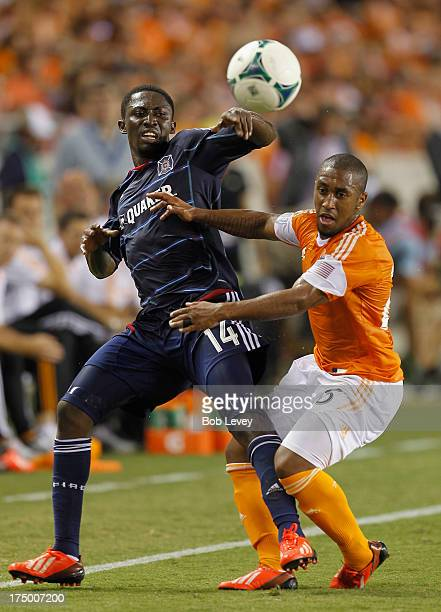 Corey Ashe of Houston Dynamo and Patrick Nyarko of Chicago Fire get tangled up going for the ball at BBVA Compass Stadium on July 27 2013 in Houston...