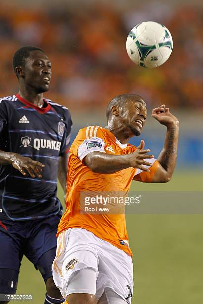 Corey Ashe of Houston Dynamo heads the ball away from Patrick Nyarko of Chicago Fire at BBVA Compass Stadium on July 27 2013 in Houston Texas