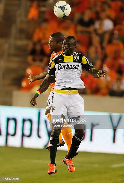 Corey Ashe of the Houston Dynamo fights for the ball against Dominic Oduro of the Columbus Crew at BBVA Compass Stadium on August 3 2013 in Houston...
