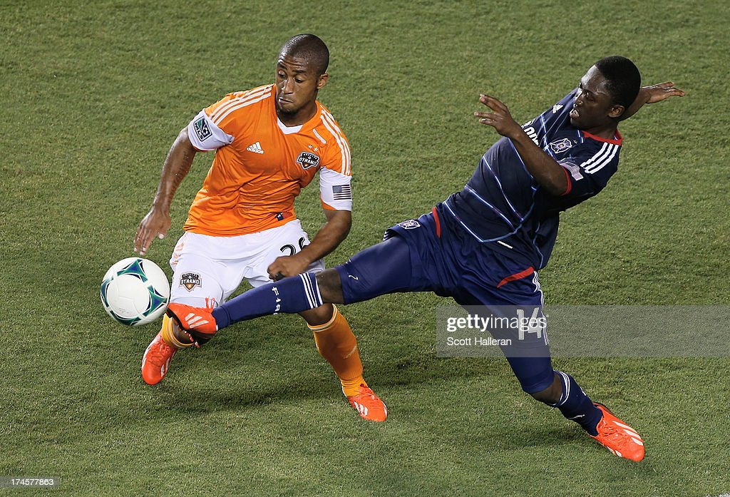 Corey Ashe #26 of the Houston Dynamo works the ball against Patrick Nyarko #14 of the Chicago Fire at BBVA Compass Stadium on July 27, 2013 in Houston, Texas.