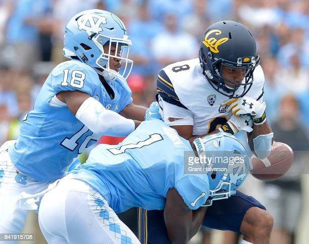 Corey Bell Jr #18 and Myles Dorn of the North Carolina Tar Heels break up a pass intended for Demetris Robertson of the California Golden Bears...