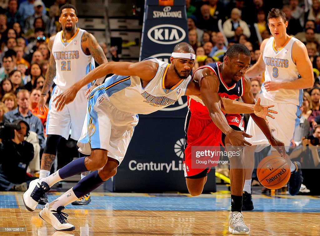 Corey Brewer #13 of the Denver Nuggets and Jordan Crawford #15 of the Washington Wizards battle for a loose ball at the Pepsi Center on January 18, 2013 in Denver, Colorado. The Wizards defeated the Nuggets 112-108.