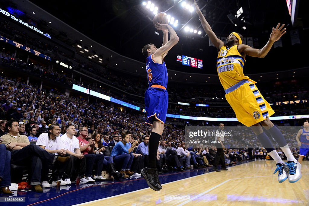 Corey Brewer (13) of the Denver Nuggets attempts a block on Steve Novak (16) of the New York Knicks during the first half of action. The Denver Nuggets play the New York Knicks at the Pepsi Center.