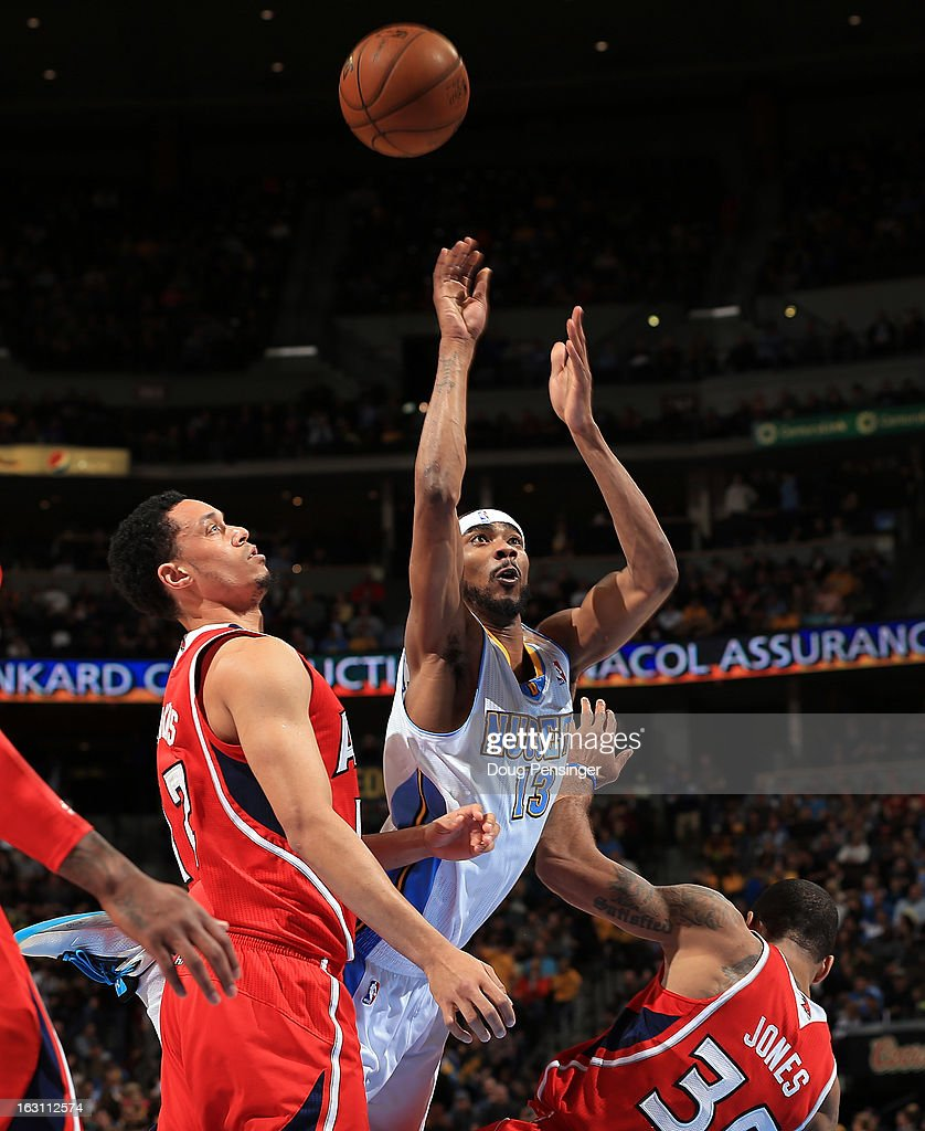 Corey Brewer #13 of the Denver Nuggets is called for an offensive foul as he collides with Devin Harris #34 of the Atlanta Hawks while going up for a shot at the Pepsi Center on March 4, 2013 in Denver, Colorado. The Nuggets defeated the Hawks 104-88.