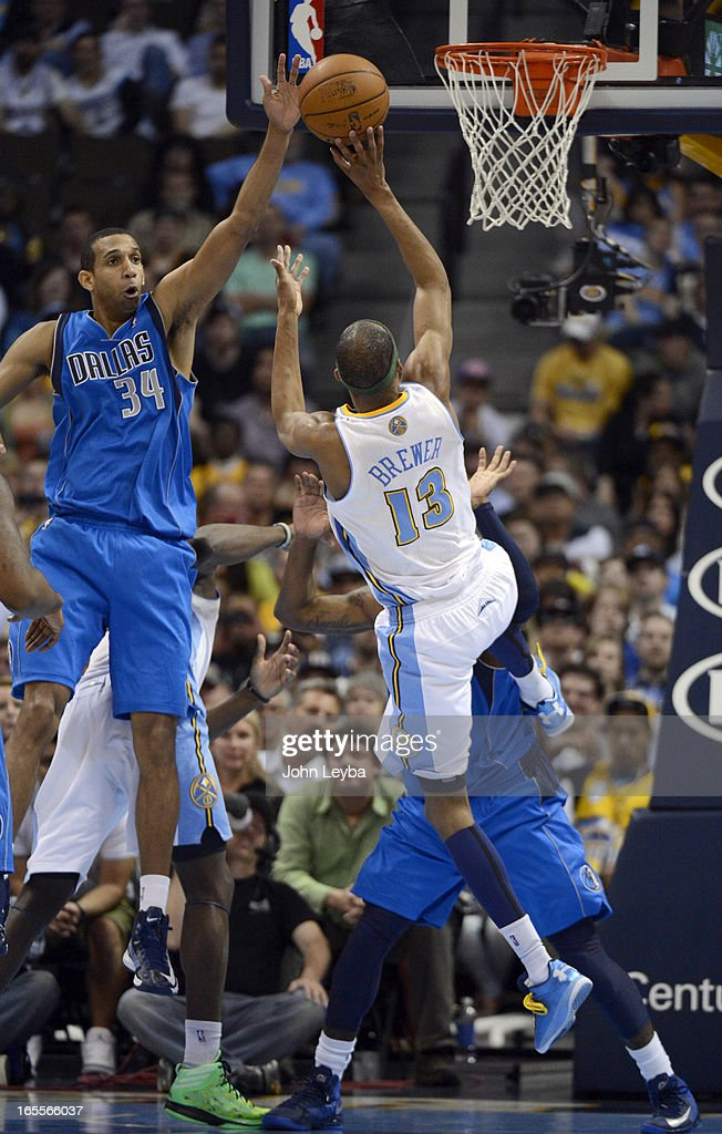 Corey Brewer (13) of the Denver Nuggets takes an off balance shot over Brandan Wright (34) of the Dallas Mavericks during the fourth quarter April 4, 2013 at Pepsi Center.