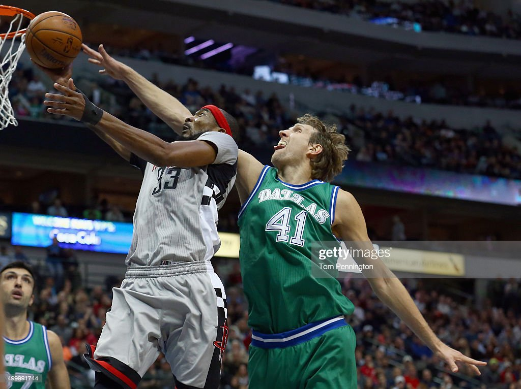 Corey Brewer of the Houston Rockets drives to the basket against Dirk Nowitzki of the Dallas Mavericks in the second half at American Airlines Center...