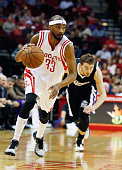 Corey Brewer of the Houston Rockets takes the basketball upcourt in front of Nik Stauskas of the Sacramento Kings during their game at the Toyota...