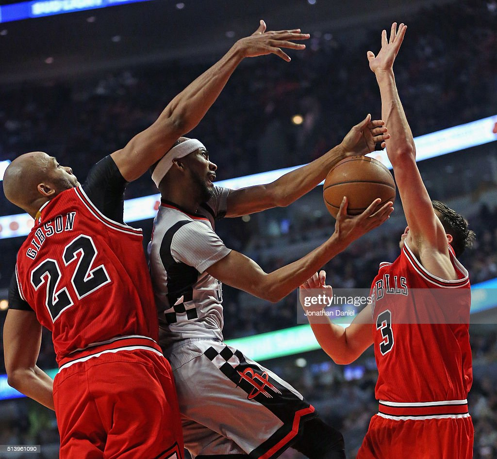 Corey Brewer of the Houston Rockets tries to get off a shot between Taj Gibson and Doug McDermott of the Chicago Bulls at the United Center on March...