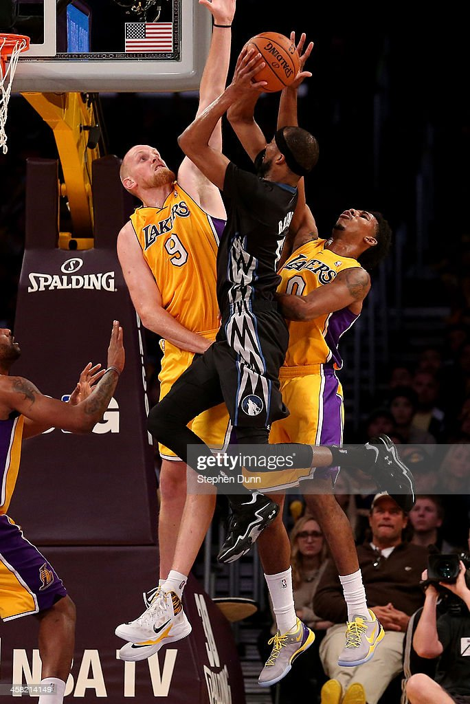 Corey Brewer #13 of the Minnesota Timberwolves goes up for a shot against Chris Kaman #9 and Nick Young #0 of the Los Angeles Lakers at Staples Center on December 20, 2013 in Los Angeles, California.