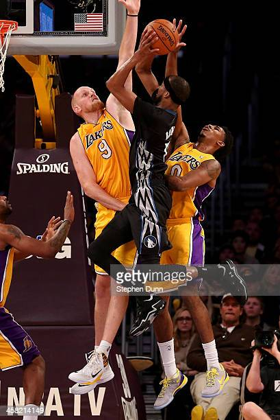 Corey Brewer of the Minnesota Timberwolves goes up for a shot against Chris Kaman and Nick Young of the Los Angeles Lakers at Staples Center on...