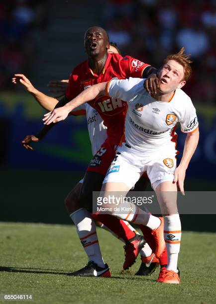 Corey Brown of Brisbane Roar competes with Papa Babacar of Adelaide United during the round 23 ALeague match between Adelaide United and the Brisbane...