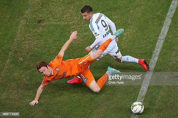 Corey Brown of the Roar and Kosta Barbarouses of the Victory compete for the ball during the round 18 ALeague match between the Brisbane Roar and...