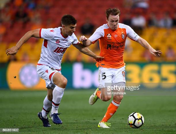 Corey Brown of the Roar contests the ball with Nathan Konstandopoulos of Adelaide United during the round two ALeague match between the Brisbane Roar...