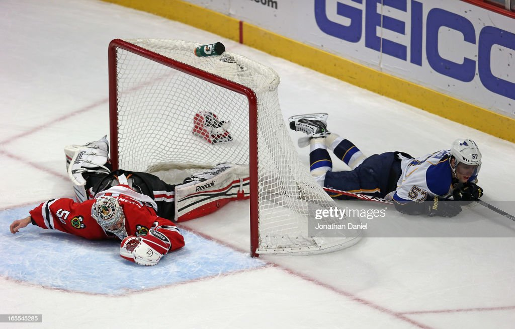 Corey Crawford of the Chicago Blackhawks and David Perron of the St Louis Blues end up on the ice after a collision at the United Center on April 4...
