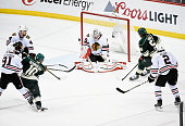 Corey Crawford of the Chicago Blackhawks blocks a shot by Jordan Schroeder of the Minnesota Wild during the third period in Game Four of the Western...