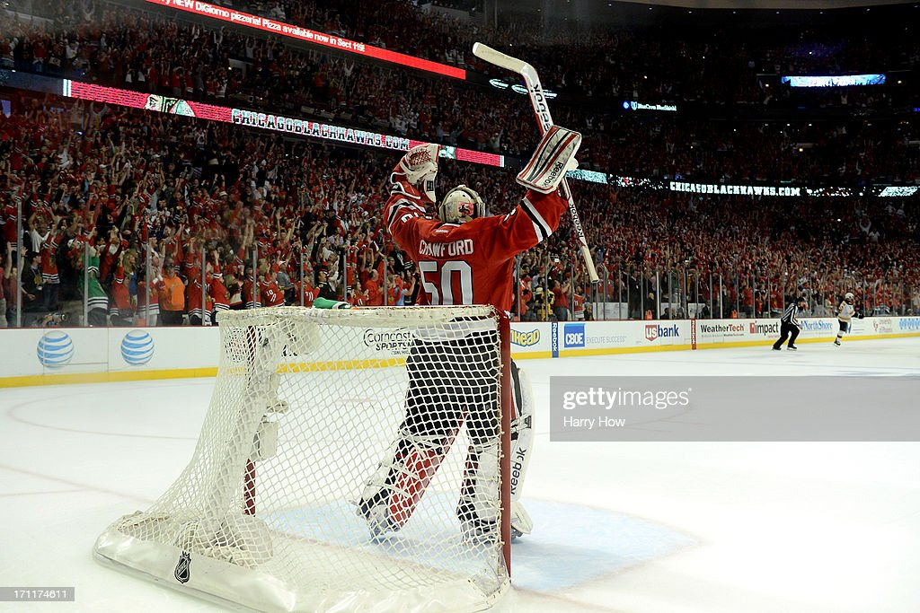 Corey Crawford of the Chicago Blackhawks celebrates an empty net goal scored by Dave Bolland late in the third period against the Boston Bruins in...