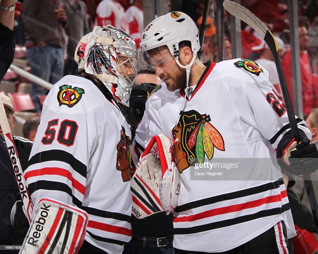 Corey Crawford #50 of the Chicago Blackhawks celebrates the 4-2 win with teammate Victor Stalberg #25 after Game Six of the Western Conference Semifinals against the Detroit Red Wings during the 2013 NHL Stanley Cup Playoffs at Joe Louis Arena on May 27, 2013 in Detroit, Michigan.