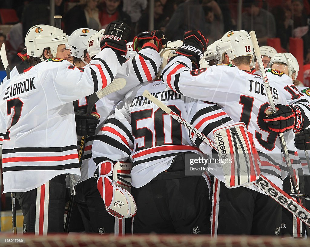 Corey Crawford #50 of the Chicago Blackhawks celebrates the shoot-out win with teammates during an NHL game against the Detroit Red Wings at Joe Louis Arena on March 3, 2013 in Detroit, Michigan. Chicago won 2-1