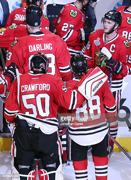 Corey Crawford of the Chicago Blackhawks celebrates with his teammate Patrick Kane after defeating the Tampa Bay Lightning 2 to 1 in Game Four of the...
