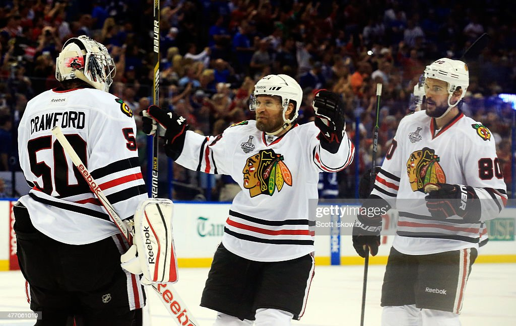 Corey Crawford #50 of the Chicago Blackhawks celebrates with teammates Antoine Vermette #80 and Kimmo Timonen #44 after defeating the Tampa Bay Lightning by a score of 2-1 to win Game Five of the 2015 NHL Stanley Cup Final at Amalie Arena on June 13, 2015 in Tampa, Florida.