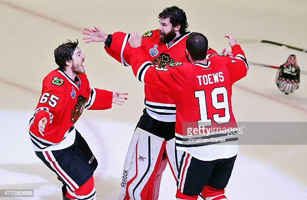 Corey Crawford of the Chicago Blackhawks celebrates with teammates Andrew Shaw and Jonathan Toews after defeating the Tampa Bay Lightning by a score...