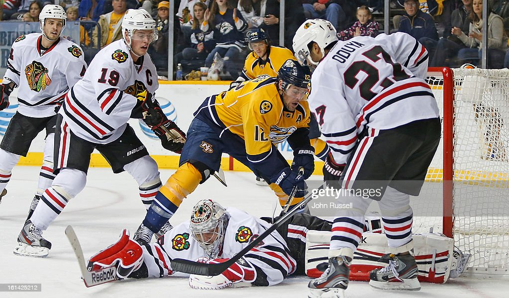 <a gi-track='captionPersonalityLinkClicked' href=/galleries/search?phrase=Corey+Crawford&family=editorial&specificpeople=818935 ng-click='$event.stopPropagation()'>Corey Crawford</a> #50 of the Chicago Blackhawks covers the puck against <a gi-track='captionPersonalityLinkClicked' href=/galleries/search?phrase=Mike+Fisher+-+Jogador+de+h%C3%B3quei+no+gelo&family=editorial&specificpeople=204732 ng-click='$event.stopPropagation()'>Mike Fisher</a> #12 of the Nashville Predators during an NHL game at the Bridgestone Arena on February 10, 2013 in Nashville, Tennessee.