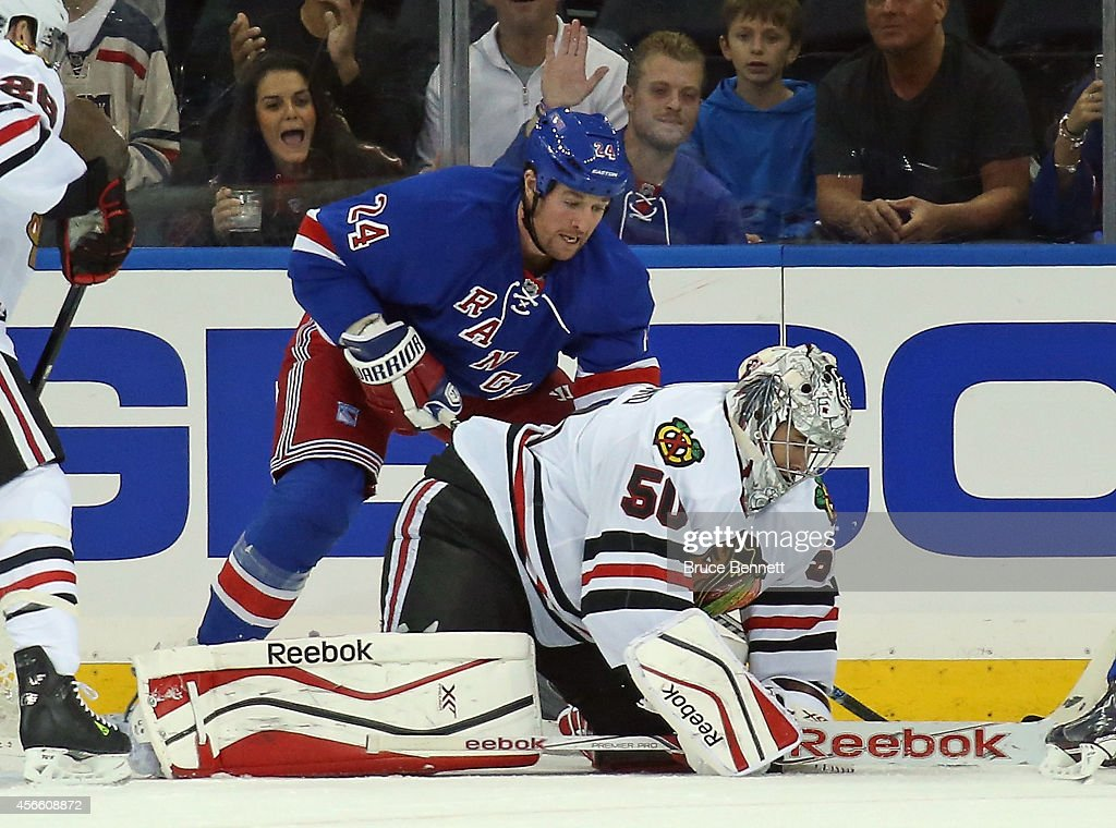 Corey Crawford of the Chicago Blackhawks covers the puck as Ryan Malone of the New York Rangers looks for the rebound at Madison Square Garden on...