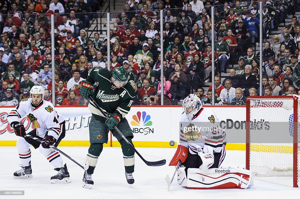Corey Crawford #50 of the Chicago Blackhawks deflects a shot by Zach Parise #11 of the Minnesota Wild as Niklas Hjalmarsson #4 of the Chicago Blackhawks looks on in Game Four of the Second Round of the 2014 NHL Stanley Cup Playoffs on May 9, 2014 at Xcel Energy Center in St Paul, Minnesota. The Wild defeated the Blackhawks 4-2.
