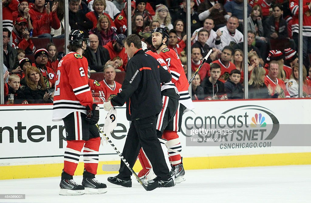 <a gi-track='captionPersonalityLinkClicked' href=/galleries/search?phrase=Corey+Crawford&family=editorial&specificpeople=818935 ng-click='$event.stopPropagation()'>Corey Crawford</a> #50 of the Chicago Blackhawks is walked off the ice in the first period against the Florida Panthers at the United Center on December 8, 2013 in Chicago, Illinois.