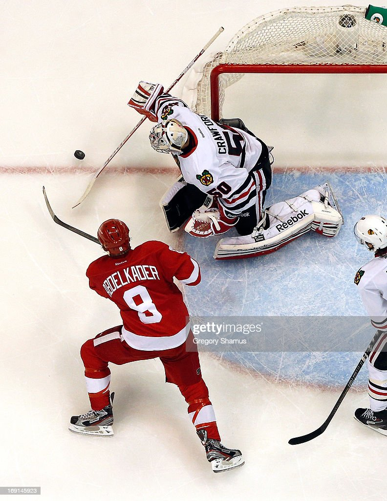 <a gi-track='captionPersonalityLinkClicked' href=/galleries/search?phrase=Corey+Crawford&family=editorial&specificpeople=818935 ng-click='$event.stopPropagation()'>Corey Crawford</a> #50 of the Chicago Blackhawks knocks the puck away from <a gi-track='captionPersonalityLinkClicked' href=/galleries/search?phrase=Justin+Abdelkader&family=editorial&specificpeople=2271858 ng-click='$event.stopPropagation()'>Justin Abdelkader</a> #8 of the Detroit Red Wings in Game Three of the Western Conference Semifinals during the 2013 NHL Stanley Cup Playoffs at Joe Louis Arena on May 20, 2013 in Detroit, Michigan. Detroit won the game 3-1 to take a 2-1 series lead.