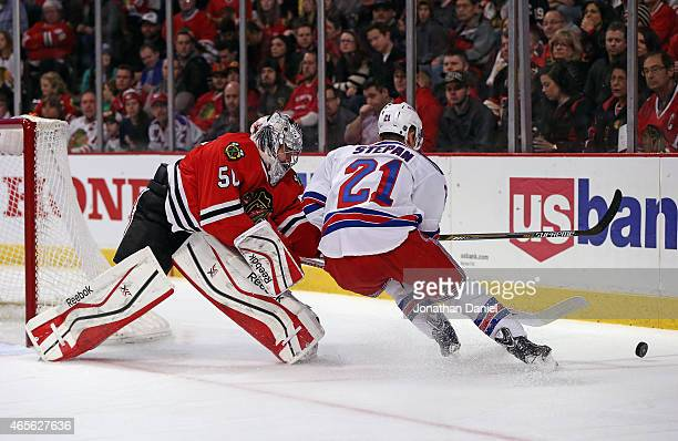 Corey Crawford of the Chicago Blackhawks knocks the puck away from Derek Stepan of the New York Rangers at the United Center on March 8 2015 in...