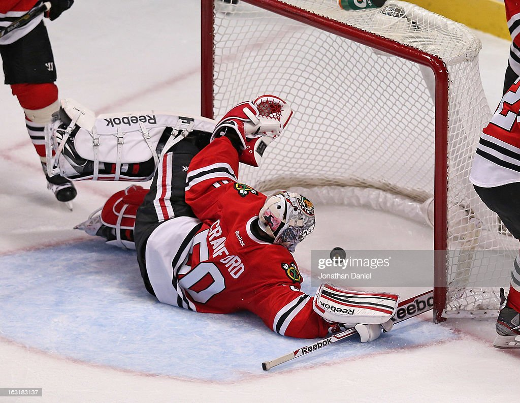 <a gi-track='captionPersonalityLinkClicked' href=/galleries/search?phrase=Corey+Crawford&family=editorial&specificpeople=818935 ng-click='$event.stopPropagation()'>Corey Crawford</a> #50 of the Chicago Blackhawks lets the puck get past him for a goal by Kyle Brodziak of the Minnesota Wild at the United Center on March 5, 2013 in Chicago, Illinois. The Blackhawks defeated the Wild 5-3.