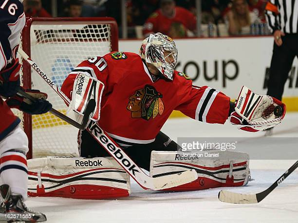 Corey Crawford of the Chicago Blackhawks makes a glove save against the Columbus Blue Jackets at the United Center on February 24 2013 in Chicago...