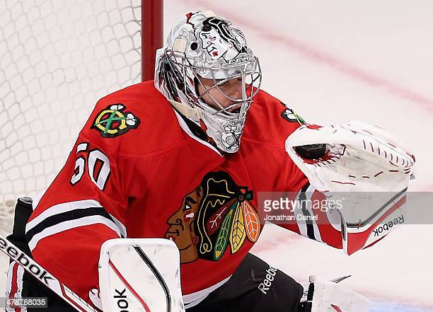 Corey Crawford of the Chicago Blackhawks makes a glove save against the Nashville Predators at the United Center on March 14 2014 in Chicago Illinois...