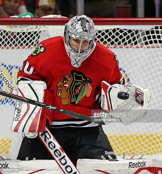 Corey Crawford of the Chicago Blackhawks makes a glove save in the second period against the Dallas Stars at the United Center on December 3 2013 in...