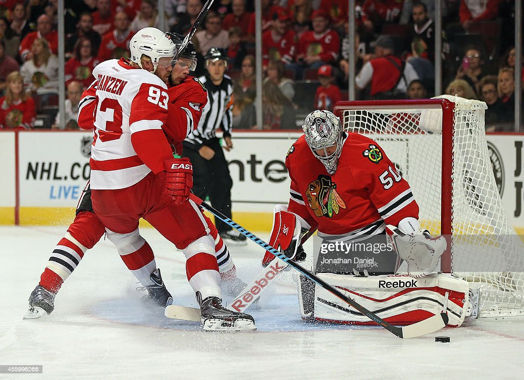 Corey Crawford #50 of the Chicago Blackhawks makes a save against <a gi-track='captionPersonalityLinkClicked' href=/galleries/search?phrase=Johan+Franzen&family=editorial&specificpeople=624356 ng-click='$event.stopPropagation()'>Johan Franzen</a> #93 of the Detroit Red Wings as <a gi-track='captionPersonalityLinkClicked' href=/galleries/search?phrase=Klas+Dahlbeck&family=editorial&specificpeople=7421197 ng-click='$event.stopPropagation()'>Klas Dahlbeck</a> #44 defends during a preseason game at the United Center on September 23, 2014 in Chicago, Illinois.