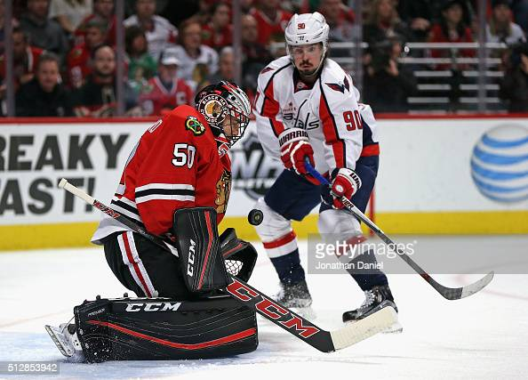 Corey Crawford of the Chicago Blackhawks makes a save against Marcus Johansson of the Washington Capitals at the United Center on February 28 2016 in...