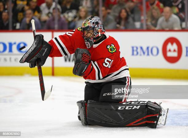 Corey Crawford of the Chicago Blackhawks makes a save against the Pittsburgh Penguins during the season opening game at the United Center on October...