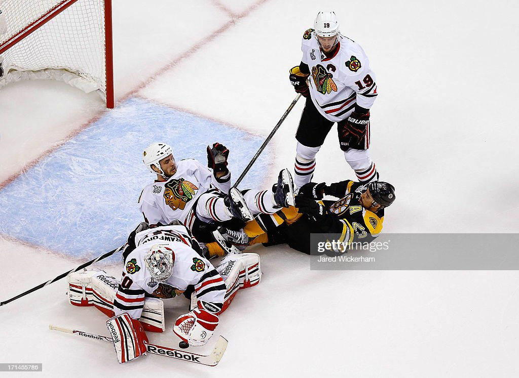 Corey Crawford of the Chicago Blackhawks makes a save as Niklas Hjalmarsson of the Chicago Blackhawks and Chris Kelly of the Boston Bruins fall to...