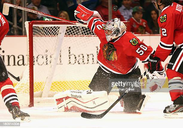 Corey Crawford of the Chicago Blackhawks makes a save as the puck sails over his head against the Detroit Red Wings during an exhibition game at...