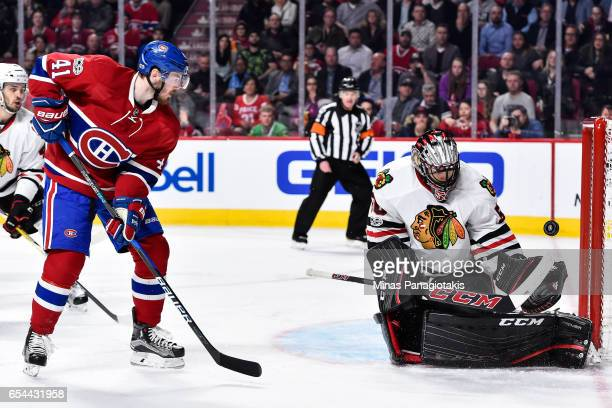 Corey Crawford of the Chicago Blackhawks makes a save near Paul Byron of the Montreal Canadiens during the NHL game at the Bell Centre on March 14...