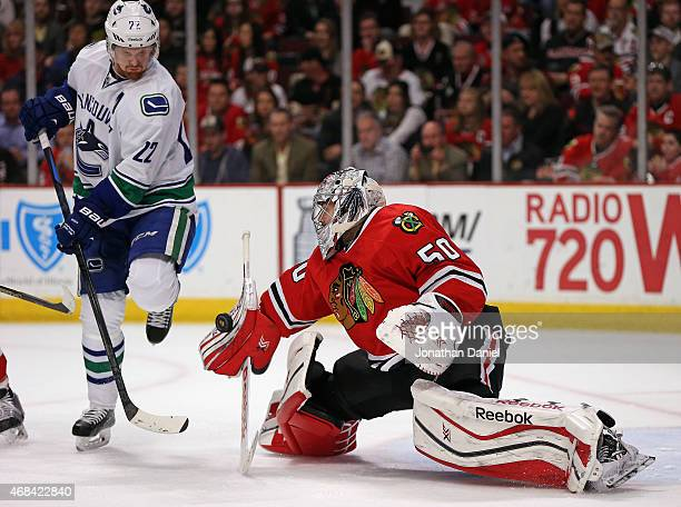 Corey Crawford of the Chicago Blackhawks makes a save next to Daniel Sedin of the Vancouver Canucks at the United Center on April 2 2015 in Chicago...