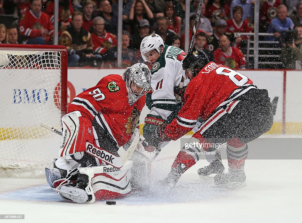 Corey Crawford #50 of the Chicago Blackhawks makes a save on a shot by Zach Parise #11 of the Minnesota Wild as Nick Leddy #8 defends in Game One of the Second Round of the 2014 NHL Stanley Cup Playoffs at the United Center on May 2, 2014 in Chicago, Illinois.