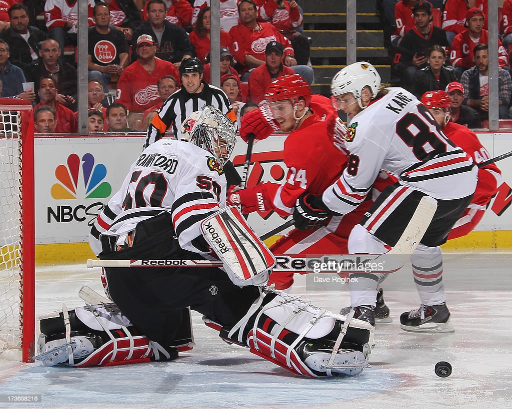 Corey Crawford of the Chicago Blackhawks makes a save on Gustav Nyquist of the Detroit Red Wings as Patrick Kane of Chicago chases during Game Six of...