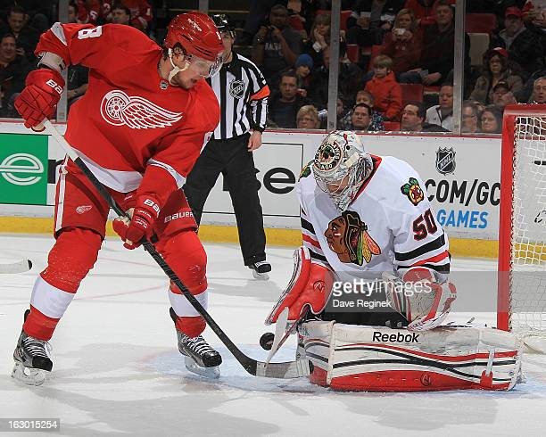 Corey Crawford of the Chicago Blackhawks makes a save on Justin Abdelkader of the Detroit Red Wings during an NHL game at Joe Louis Arena on March 3...