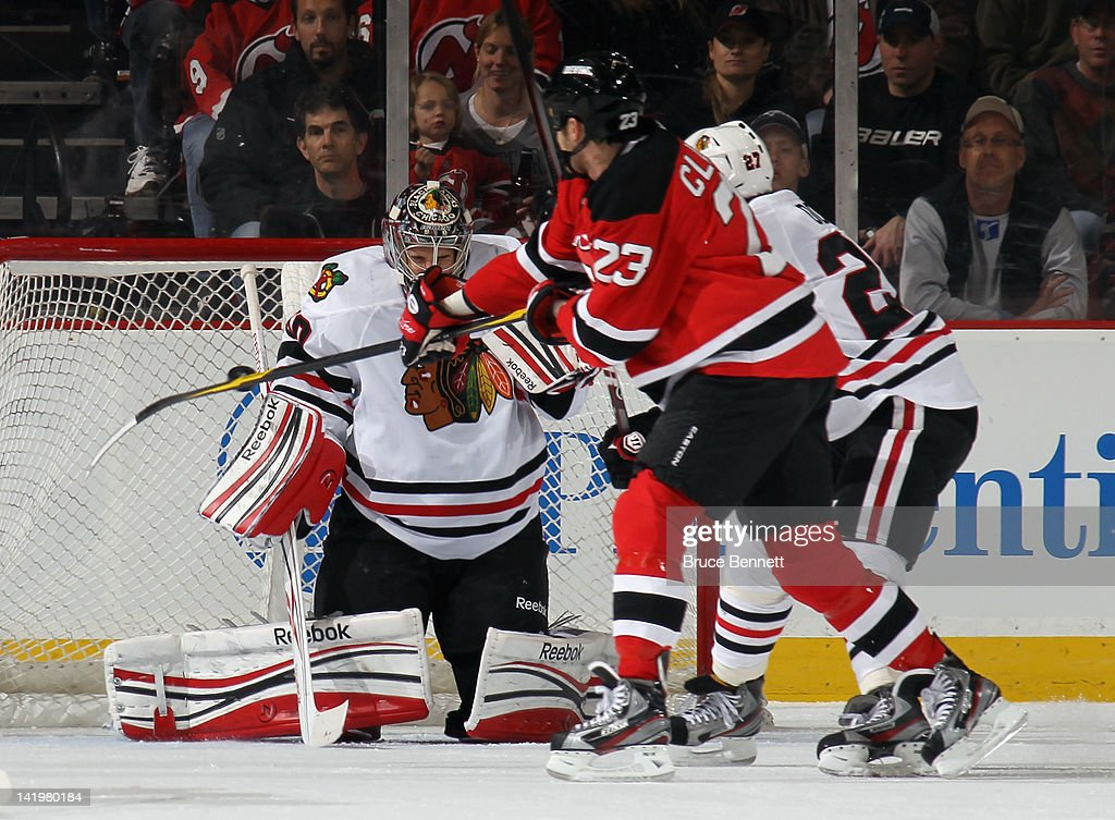 <a gi-track='captionPersonalityLinkClicked' href=/galleries/search?phrase=Corey+Crawford&family=editorial&specificpeople=818935 ng-click='$event.stopPropagation()'>Corey Crawford</a> #50 of the Chicago Blackhawks makes the save as David Clarkson #23 of the New Jersey Devils looks to defelect the puck at the Prudential Center on March 27, 2012 in Newark, New Jersey. The Devils defeated the Blackhawks 2-1 in the shootout.