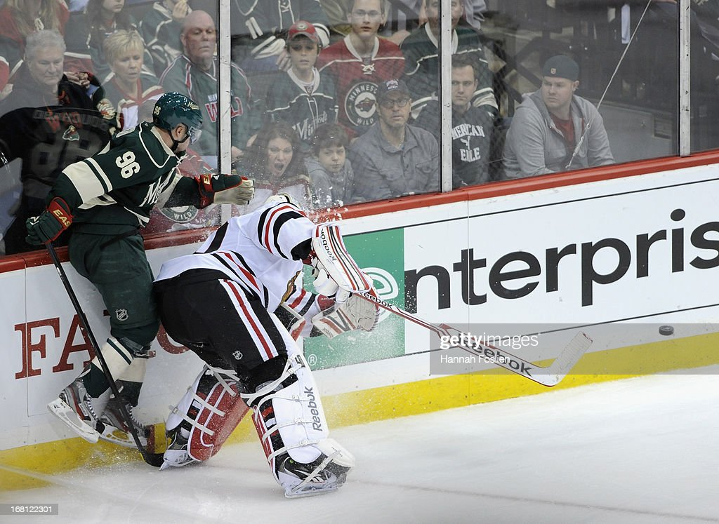 <a gi-track='captionPersonalityLinkClicked' href=/galleries/search?phrase=Corey+Crawford&family=editorial&specificpeople=818935 ng-click='$event.stopPropagation()'>Corey Crawford</a> #50 of the Chicago Blackhawks passes the puck away from <a gi-track='captionPersonalityLinkClicked' href=/galleries/search?phrase=Pierre-Marc+Bouchard&family=editorial&specificpeople=204628 ng-click='$event.stopPropagation()'>Pierre-Marc Bouchard</a> #96 of the Minnesota Wild during the third period of Game Three of the Western Conference Quarterfinals during the 2013 NHL Stanley Cup Playoffs at Xcel Energy Center on May 5, 2013 in St Paul, Minnesota. The Wild defeated the Blackhawks 3-2 in overtime.