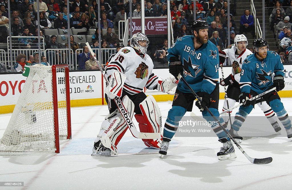 Corey Crawford #50 of the Chicago Blackhawks protects the net against Joe Thornton #19 of the San Jose Sharks at SAP Center on February 1, 2014 in San Jose, California.