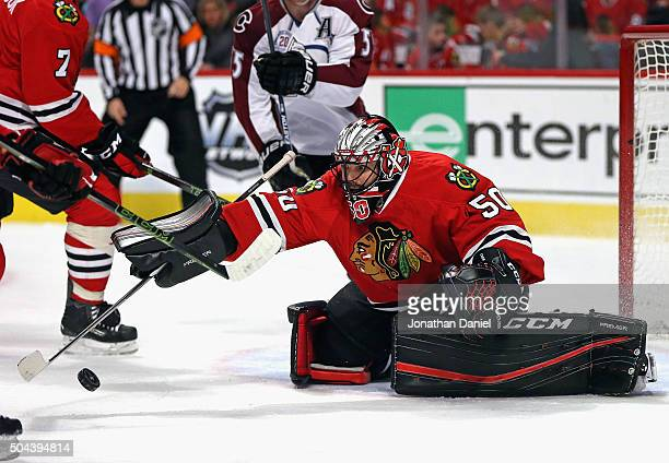 Corey Crawford of the Chicago Blackhawks reaches to make a save against the Colorado Avalanche at the United Center on January 10 2016 in Chicago...